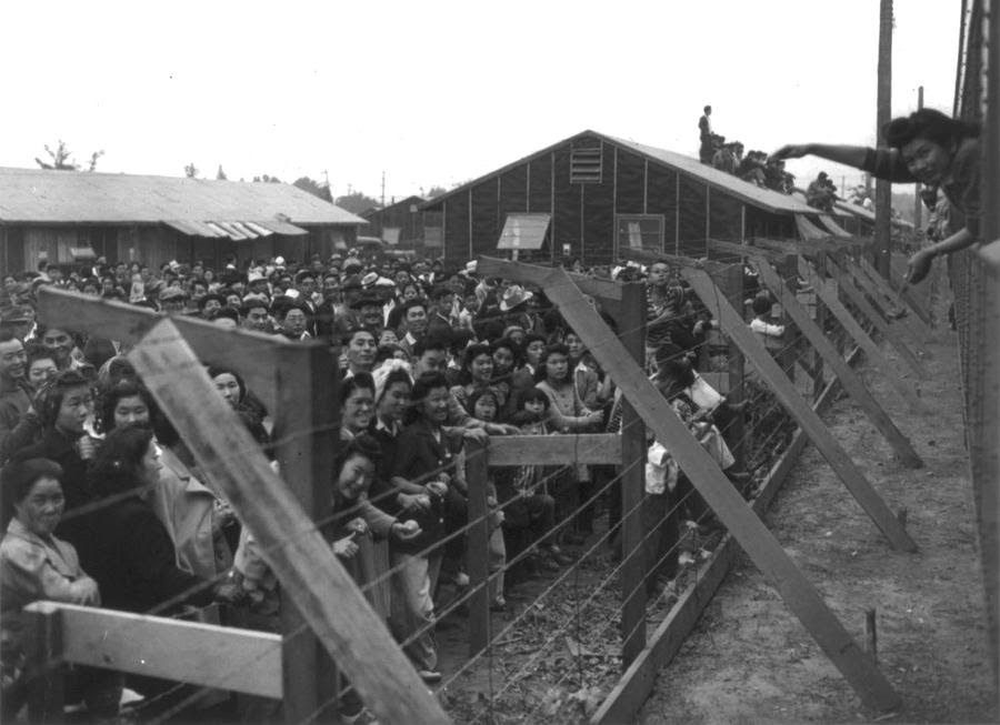 A crowd of Japanese Americans stand behind a barbed-wire fence, waving to departing friends on train leaving Santa Anita, California.